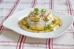 Healthy dinner - rice with roasted tofu served on chequered tablecloth Stock Photos