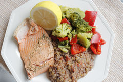 Healthy Dinner of Salmon Vegetables and Quinoa. Poached wild salmon with dill herb, tricolor quinoa, lentil and vegetables recipe with green broccoli florets and Royalty Free Stock Photo