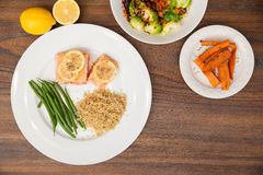 Healthy dinner seen from above. Flat lay of a hearty dish of salmon, green beans and quinoa, served with a green salad and some sweet potatoes on a wooden table Stock Images