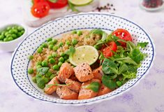 Slices of grilled salmon, quinoa, green peas, tomato, lime and lettuce leaves. Healthy dinner. Slices of grilled salmon, quinoa, green peas, tomato, lime and stock photos