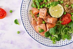 Healthy dinner. Slices of grilled salmon, quinoa, green peas, tomato, lime and lettuce leaves. Flat lay. Top view royalty free stock photo