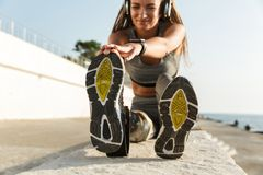 Healthy disabled athlete woman. With prosthetic leg doing stretching exercises while sitting at the beach and listening to music with headphones stock photography