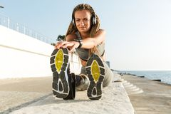 Healthy disabled athlete woman with prosthetic leg. Doing stretching exercises while sitting at the beach and listening to music with headphones royalty free stock photography