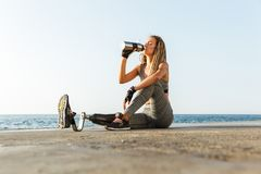 Healthy disabled athlete woman with prosthetic leg. Sitting at the beach and drinking water from a bottle royalty free stock photo