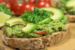 Healthy dish with avocado - guacamole. Healthy homemade guacamole. Traditionally mexican dish. Lime, tomato, parsley on the background Stock Photo