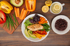 Healthy dish with chicken seen from above. Top view of a dish with chicken and vegetables served with black beans and shown with some of its ingredients Stock Photo
