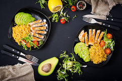 Healthy dish with chicken, tomatoes, avocado, lettuce and lentil on dark background. Dinner. Flat lay. Top view royalty free stock images