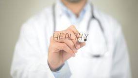 Healthy, Doctor writing on transparent screen Stock Images