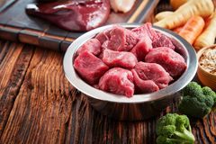 Healthy dog food ingredients on rustic wood. With a metal bowl filled with chopped raw beef, liver and assorted fresh vegetables royalty free stock photography