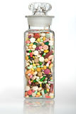 A Healthy Dose of Medicine. A vintage glass full of pills and capsules Royalty Free Stock Images