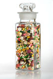 A Healthy Dose of Medicine. A vintage glass full of pills and capsules Stock Photos