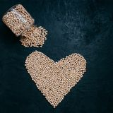 Healthy dried garbanzo or chickpeas spilled from glass jar, heart shaped organic raw beans isolated over black background. Living. Food and wellness royalty free stock images