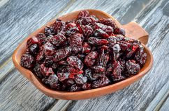 A healthy dried snack. Cranberries in a brown wooden bowl royalty free stock photography