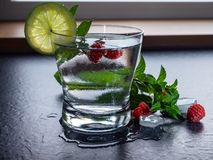 Healthy drink / cocktail with cold water, raspberry, mint, lime and ice cubes to detox. Glass of refreshment after a workout or a yoga session. Vegetarian royalty free stock photos