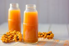 Healthy drink - sea buckthorn juice in a glass bottle over wooden table. Healthy drink - sea buckthorn juice in a glass bottle over wooden table Royalty Free Stock Photography