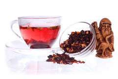 Healthy drink in transparent cup with asian idol. Healthy fruit tea in a transparent cup and saucers with dry fruit tea, and idol of prosperity statuette stock image