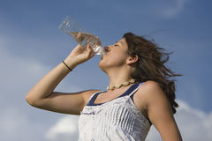 Healthy Drinking. Young healthy teenage girl drinking a bottle of water outside Stock Image