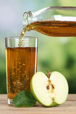 Healthy drinking apple juice pouring from apples into a glass Royalty Free Stock Photos