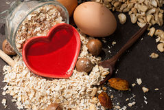 A Healthy Dry Oat meal with nut and Red heart in a wooden spoon Stock Images
