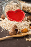 A Healthy Dry Oat meal with nut and Red heart in a wooden spoon Stock Photo
