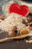 A Healthy Dry Oat meal with nut and Red heart in a wooden spoon Stock Photography