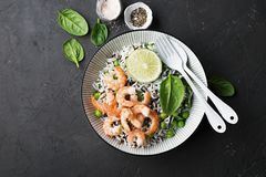 Healthy easy food. Wild rice and basmati rice with young green peas, royal prawns and yellow cherry tomatoes in white Royalty Free Stock Images
