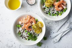 Healthy easy food. Wild rice and basmati rice with young green peas, royal prawns and yellow cherry tomatoes in white Royalty Free Stock Image