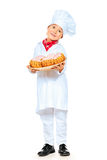 Healthy eat. Full length portrait of a little boy cook holding delicious pastries. Different occupations. Isolated over white background royalty free stock image