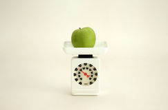 Healthy eating. A green apple on a scale against a white background Royalty Free Stock Image