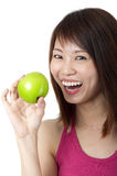 Healthy Eating. Beautiful young woman eating green apple. Isolated over white Royalty Free Stock Image