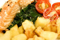 Healthy eating. Close up of salmon and spinach with cherry tomatoes and roast potatoes Royalty Free Stock Image
