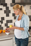 Healthy eating. Attractive blond woman eating healthy food while pregnant Stock Photo
