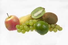 Healthy eating. Banana, apple, kiwi, grapes and lime on white background Stock Images