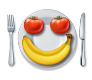 Healthy Eating. And health diet with a dinner plate fork and knife and tomatoes and a banana looking as a happy smiling face fighting obesity on a white Royalty Free Stock Photos
