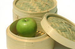 Healthy Eating Asia. Dim sum steam baskets and with a green apple symbolising healthy eating asian style Stock Images