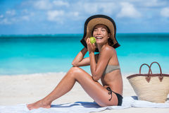 Healthy eating beach woman on summer vacation. Healthy eating Asian woman on beach travel vacation biting in fresh apple fruit as a weight loss diet for a bikini Royalty Free Stock Photo