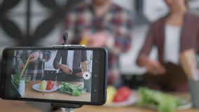 Healthy eating blog, mobile phone makes video recording live how bloggers man and woman cook preparing healthy meals stock video footage