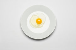 Healthy eating and Breakfast Topic: raw egg lays on a white plate on a white isolated background in studio top view Stock Photography