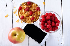 Healthy eating, cereals, apple and raspberries on a white wooden. Table. Phone on the dining table Royalty Free Stock Photo