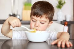 Healthy eating and children concept. Handsome small child eats with great appetite delicious porridge prepared by mother, holds bi stock images
