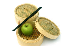 Healthy Eating Chinese Style. Chopsticks, dim sum steam baskets and chopsticks with a green apple symbolising healthy eating asian style Stock Photos