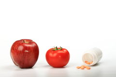Healthy eating choice. Apple tomato and vitamin pills as the symbol of healthy eating choice Royalty Free Stock Images