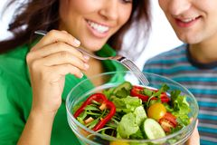 Healthy eating. Close-up of young couple eating vegetable salad from glass bowl Royalty Free Stock Photo