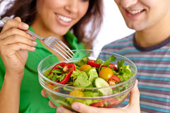 Healthy eating. Close-up of young couple eating vegetable salad from glass bowl Royalty Free Stock Images