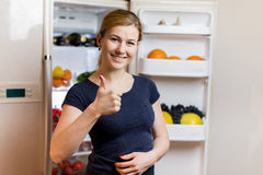Healthy Eating Concept . Beautiful Young Woman near the Refrigerator with healthy food. Fruits and Vegetables Royalty Free Stock Photography