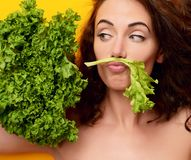 Healthy eating concept. Dieting. Woman hold lettuce looking at the corner. On yellow background royalty free stock images