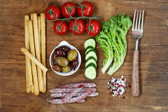 Healthy eating concept food set - sausages, bread sticks, tomatoes, cucumbers, lettuce, olives Stock Photo