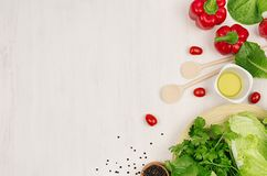 Healthy eating concept - fresh green salad, cherry tomatoes, paprika, spinach and olive oil on white wood board, top view. Stock Photos