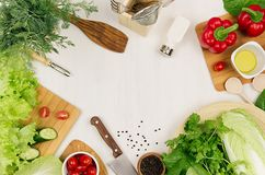 Healthy eating concept - fresh raw green salad, cherry tomatoes, paprika, spinach, cabbage and olive oil on white wood board, top. View Royalty Free Stock Photos