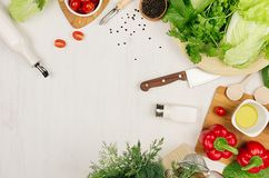 Healthy eating concept - fresh raw green salad, cherry tomatoes, paprika, spinach, cabbage and olive oil on white wood board, top. View Royalty Free Stock Photo